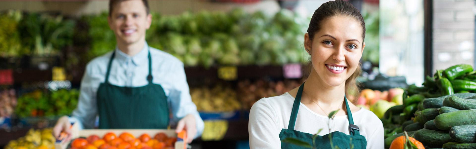 Supermarket workers selling oranges
